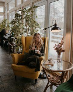 Frau entspannt in skandinavischem Ohrensessel.