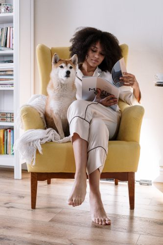 Skandinavischer Sessel: Frau und Hund entspannen gemeinsam in gelbem Ohrensessel.